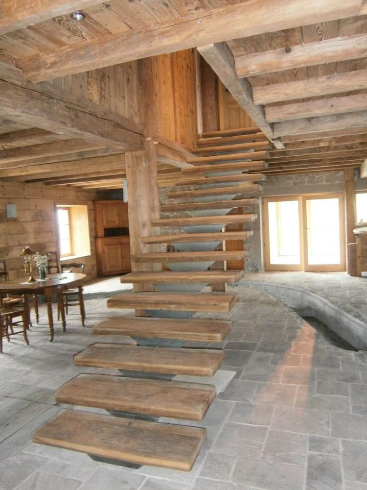 Escalier limon central en vieux bois et acier. Plafond mur et poutrage